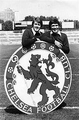 August 1980: Chelsea FC manager Geoff Hurst and assistant manager Bobby Gould showing off the club's newly-painted badge