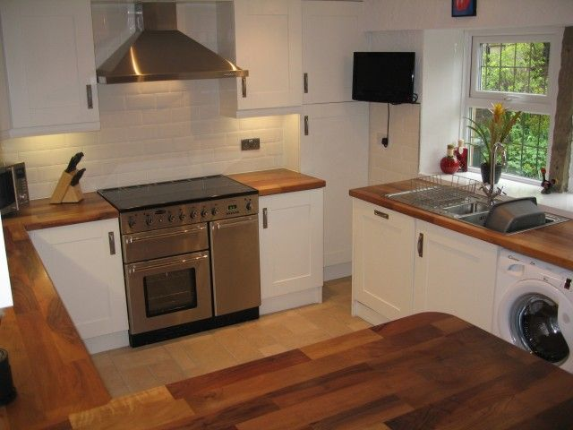 Country Style Kitchen - Hand Painted White Shaker Oak doors with solid Walnut worktops and Cream bevelled brick tiles.