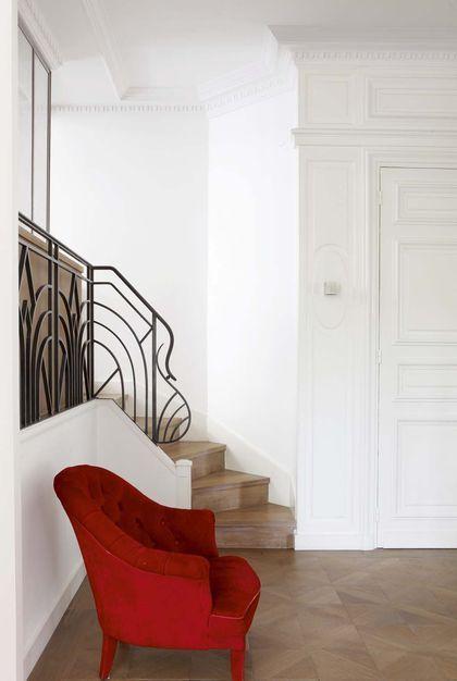 """Un fauteuil rouge vintage sur parquet """"croix de Vienne"""" en chêne"""