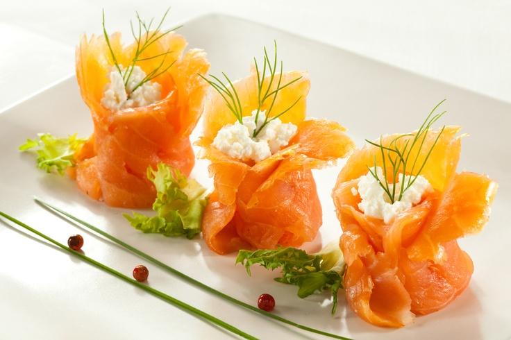 Sakiewki z wędzonego łososia z sosem serowym. Składniki:  •wędzony łosoś   •twarożek  •pietruszka  •cebula  •szczypiorek  •Sos serowy Tarsmak.  Wykonanie: posiekać cebulę i pietruszkę. Posiekane składniki oraz twarożek nałożyć na środek plastrów łososia, a następnie polać  Sosem serowym Tarsmak.  Sparzyć szczypiorek i związać nim plastry łososia w kształt sakiewki. Twarożek możemy zastąpić także posiekanym, ugotowanym na twardo jajkiem.