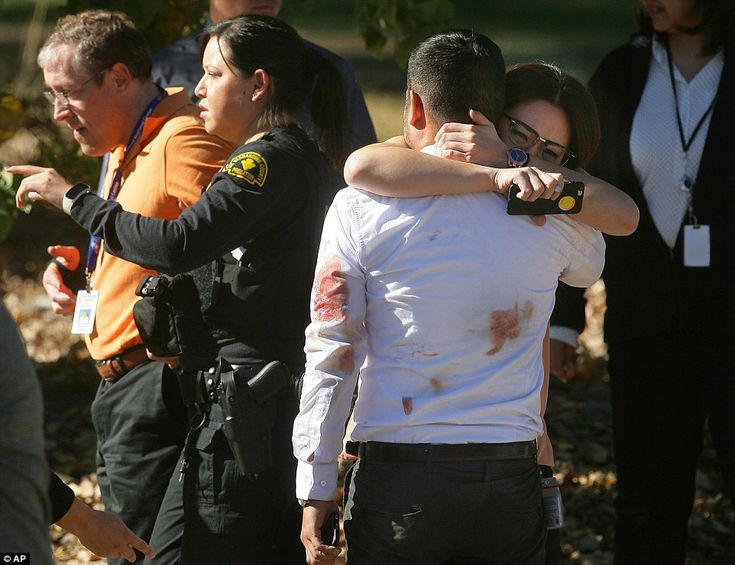 A couple embraces following the shooting at the conference building at the same site as a education center for disabled children