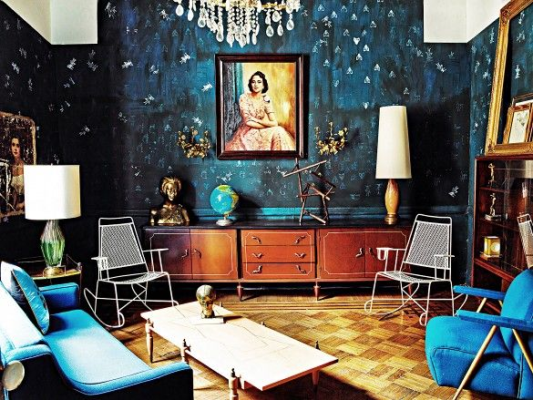 Indigo walls and blue furniture set the mood for a beautiful living room with wire rocking chairs, globe, and large oil painting portrait.