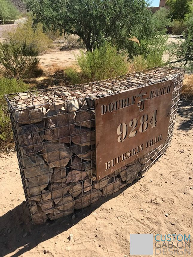 Curved gabion wall with house number.