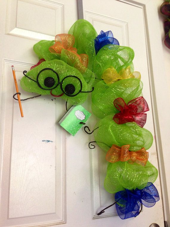 Adorable back to school bookworm wreath. He can hang on a door or stand. Made with line green mesh, various mesh colored bows. He has glasses