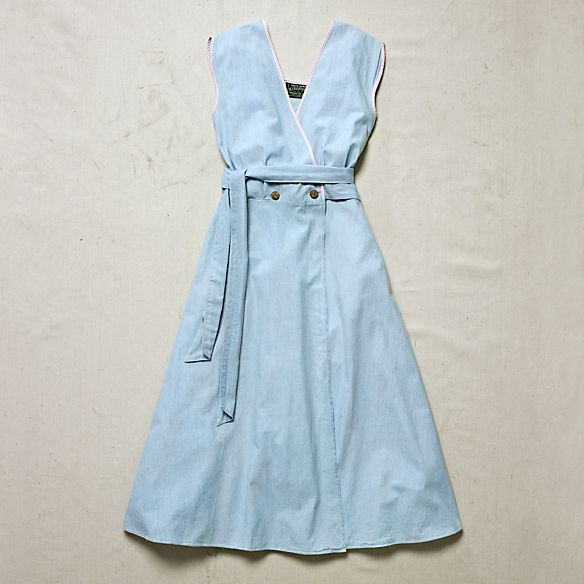 By using chambray and gingham, two fabrics popular early in the 20th century West, Ralph Lauren created a dress that exemplifies his pure American sensibility.  Circa 1990.  Gingham piping at the edges and cap sleeves.  Wrap silhouette. Flower-detailed buttons. Self-tie belt.  Label reads size 9. Measurements: 89 cm chest; 72 cm waist; 106 cm length.  100% cotton.