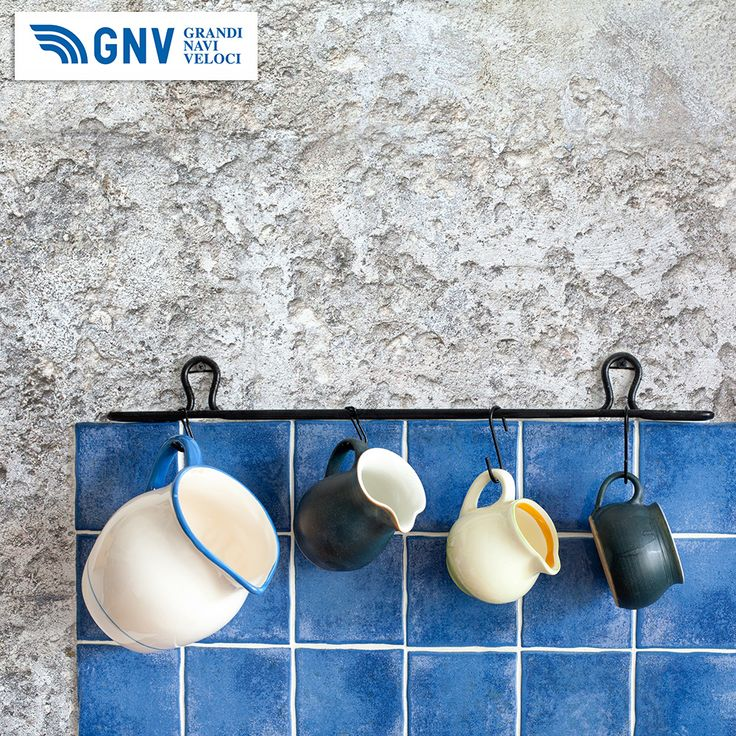 #Kitchen #accessories. #Hanging jugs. Retro #design #ceramic #pitchers. #White, #dark#green, #light#yellow and #green #color. #Blue #tiles, #aged #textured #stone wall background. Discover #GNV routes in our website:www.gnv.it/en/