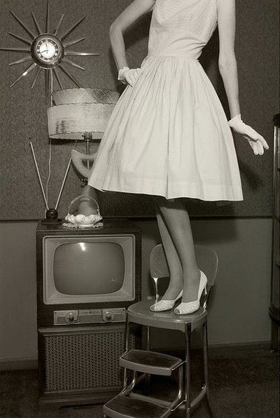 Just look at all the iconic items of the 50's in this one pictures.  Rabbit ears, style of TV, woman's dress, nylons, and gloves, kitchen stool, the lamp, milk glass dish on a doily and the clock on the wall.  All things I grew up with in the '50's
