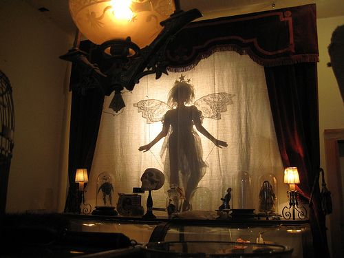 """Fairy shade. This is a really strange picture. That fairy is way too big to be """"fairy-sized,"""" but it's still cool. Then there's that random skull that adds a sense of macabre. And other things under glass. Why is this giant fairy lingering in this weird place?"""