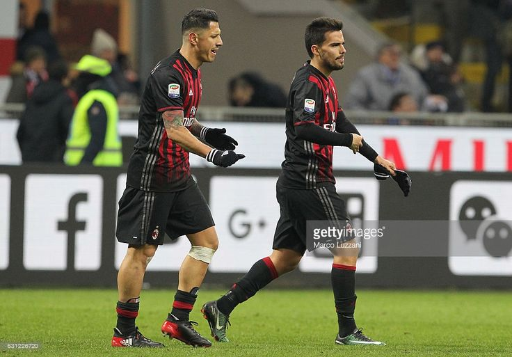 Gianluca Lapadula (L) of AC Milan disputes with his team-mate Suso (R) at the end of the Serie A match between AC Milan and Cagliari Calcio at Stadio Giuseppe Meazza on January 8, 2017 in Milan, Italy.