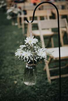 A Rustic Country Farm Wedding | Kaylon + John info@warrenwoodmanor.com Daisies and baby's breath in mason jar on shepard's hooks for aisle at rustic country outdoor wedding