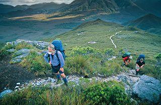 South Coast Track, Tasmania. Three people walking up  a mountain side
