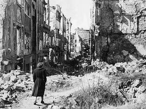 Eine Frau geht 1945 durch die Ruinen von Dresden
