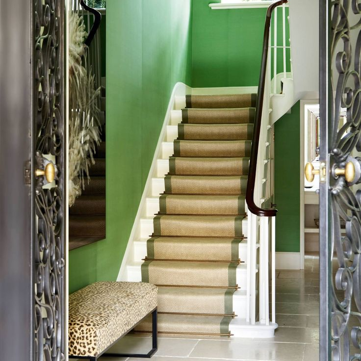 """In this 'metropolitan luxe' home in Regent's Park, London, interior decorator Louise Jones has used a natural-coloured jute runner with olive green borders and brass stair rods to complement the hallway's green silk wallcovering from de Gournay.   Like this? Then you'll love  [link url=""""http://www.houseandgarden.co.uk/interiors/small-flat-ideas""""]How to decorate a flat[/link]"""