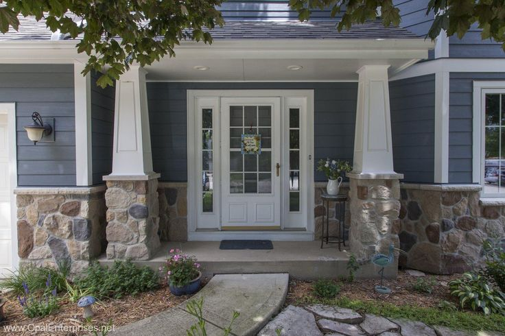 Inviting elegant entry on blue house with stone accents and decorative columns #OpalCurbAppeal