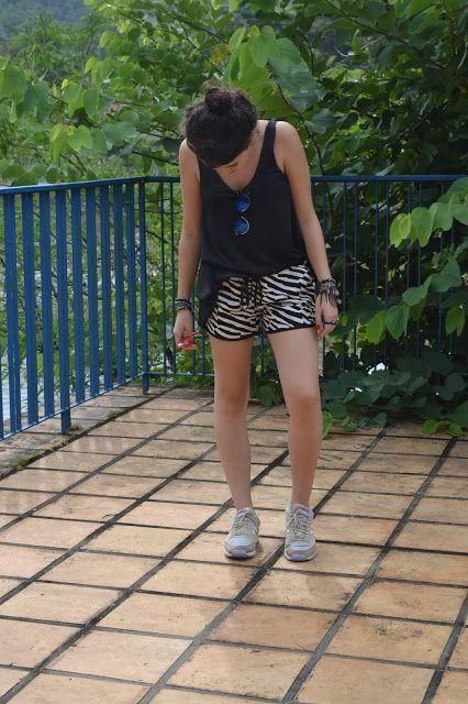 Shorts curtinho preto e branco, estilo esportivo; Regata preta básica; Tênis Adidas nude e lilás; óculos RayBan espelhado azul