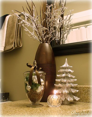 """A Bathroom Gets Some Silver """"Frostiness"""" For Christmas. Silver Ornaments, Faux Greenery And Brown Shredded Paper In An Apothecary Jar."""