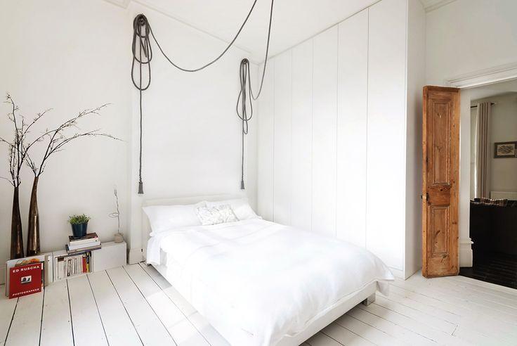 Il pavimento di legno grezzo e le lampadine sospese con cavi a vista nella bella e luminosa camera da letto  danno un tocco industriale all'ambiente.