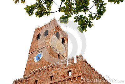 Photo made in Noale in the province of Venice (Italy). Noale is a town of ancient origin, which is located about halfway between the cities of Padua and Treviso. The picture shows the top of the clock tower and the medieval south west side of the crenellated walls of the building to which the tower is part. At the top of the image glimpsed the Fogie of an oak.