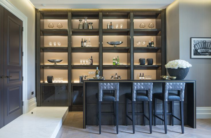 The elegantly accessorised shelving acts as a statement feature within our design of this contemporary bar, whilst the trio of beautifully upholstered bespoke bar stools in plush Zinc Textile fabric add a touch of luxury.