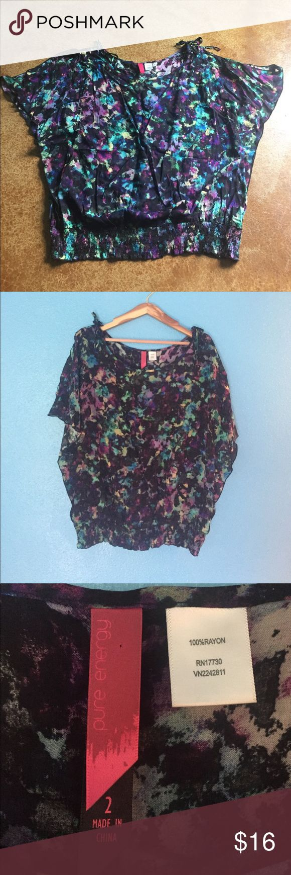 Pure Energy 2X cold shoulder top This size 2 (2X) Pure Energy top has a bright abstract pattern and black base, cold shoulder glitter sleeves with a scoop neck and decorative ties. The elastic band at waist gives adjustable fit. Laid flat it measures 24 inches at bust, 20 at waist band (with lots more stretch there) and 27 inches shoulder to hem. Gently used and from a smoke free home. Pure Energy Tops Blouses