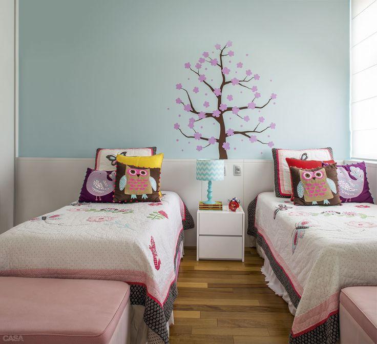 Pufes (Tapeçaria Moderna) colocados ao pé das camas guardam as almofadas (Pottery Barn, as estampadas, e Sala Design, as lisas) na hora de dormir. O tom das paredes é da Sherwin-Williams, cor Take Five, ref. SW6513*. Adesivo da Elitize.