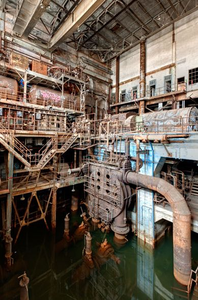 Image: Scott Haefner Stagnant green water has pooled at the bottom of this section of the power plant, no doubt hastening the decay of the machinery. In this photograph, you can see that rust has covered almost all of the metal parts.