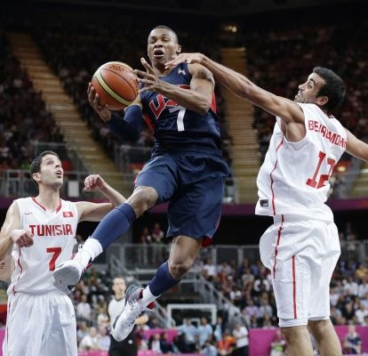 Team USA's Russell Westbrook (7) is grabbed by Tunisia's Makram Ben Romdhane (12) as he tries to score during the first half of a preliminary men's basketball game at the 2012 Summer Olympics. (July 31, 2012) Photo Credit: AP