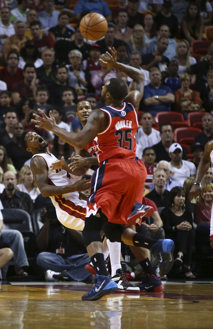 After knocking Maimi Heat's Udonis Haslem (40) to the floor Washington Wizards' Trever Booker rebounds the ball during the first half of an NBA basketball game in Miami, Sunday, Nov. 3, 2013. (AP Photo/J Pat Carter)