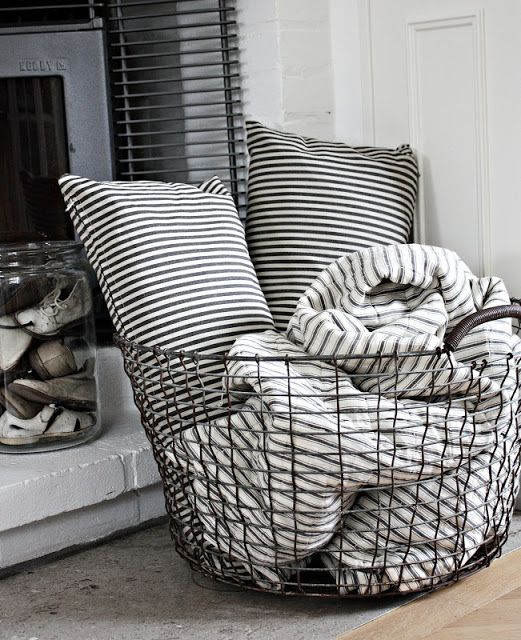 wire basket near the fireplace for blankets and pillows More