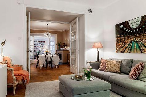 Sala de estar de um apartamento nórdico, sofá cinza, poltrona laranja, paredes brancas e vista para sala de jantar.
