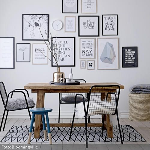 Eine Ansammlung von Bilderrahmen kann die Wirkung eines Raumes entscheidend beeinflussen. EIne Mischung aus Typographien und abstrakten Motiven wirkt modern und chic. Die Drahtstühle mit Lammfell sind optisch und haptisch ein fairer Kompromiss zwischen modern-kantig und flauschig-kuschelig.