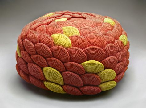 A flower shaped pouf made of a 156 crocheted orange and yellow polyester shapes.
