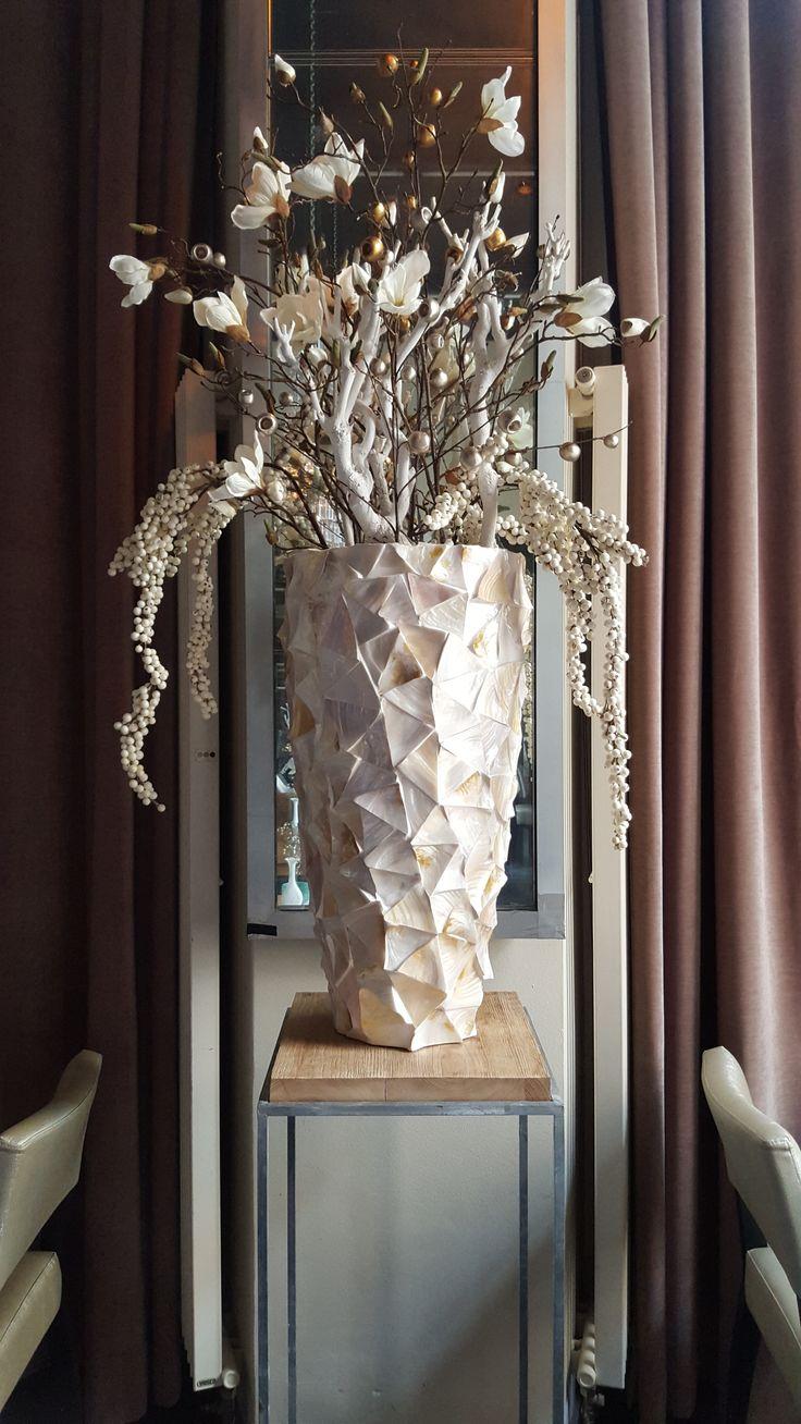 Prachtige vaas van capiz. Opgemaakt met kunstbloemen en witte takken. Restyling Wasserman Brasserie naar Vinerie