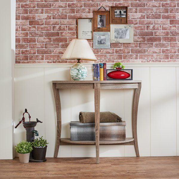 The Three Posts Shandaken Console Table in Cappuccino finish is made in a half-moon shape with stylish three legs and an open shelf at the bottom. The open shelf has space to place your display item like a flower pot, a showpiece or books. The top has space for your decorative items, lamp and your photo frame.   This table stands on three legs and also has a support panel at the back for rigid strength. This table needs assembly as it does not come assembled. The weighing capacity of this…