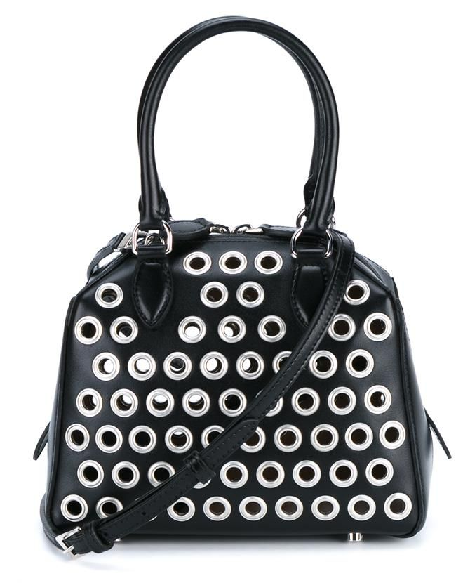 This black Azzedine Alaia mini bowling 'Trapeze' leather bag will be a practical addition to your evening wear portfolio this season. Beautifully crafted from leather, this compact piece features a double top zip closure, adjustable and detachable shoulder strap and silver-tone grommets throughout. Complete with two top handles, wear this exquisite Italian design with a black a-line skirt and metallic jumper to channel a ravishing party look.