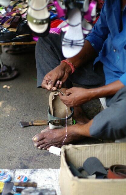 2013/03/24インド・マイソール。 とうとうサンダル右足の底がはずれて歩行不能。町の靴屋屋台へ修理に出す、の図。縫うしかないね!って、縫ってもらってるとこ。