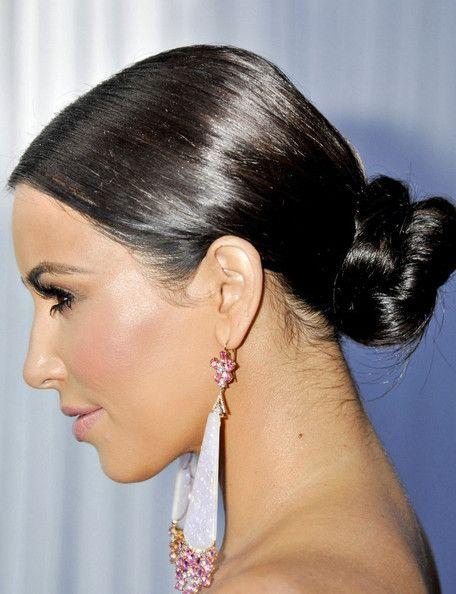 Kim Kardashian wears a slick bun at the nape of her neck. Love these earrings! #kimkardashian #hair