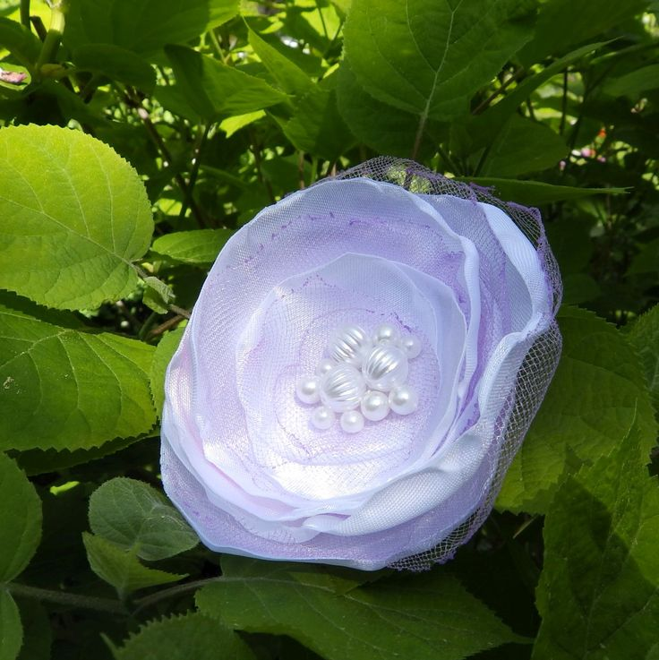 Odette Něžná bílo fialková brož nebo spona do vlasů. Průměr je 9 cm. Květ je přidělaný na univerzálním brožovém můstku, takže jej můžete použít jako sponu do vlasů, nebo jako brož. Jako bonus ke každé květině dostanete zdarma skládanou origami krabičku.
