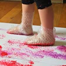 Je legt een groot vel papier op de grond en plakt het vast. Je doet van dat bolletjesplastic aan hun voeten en laat ze in de verf stappen en dan op het papier.