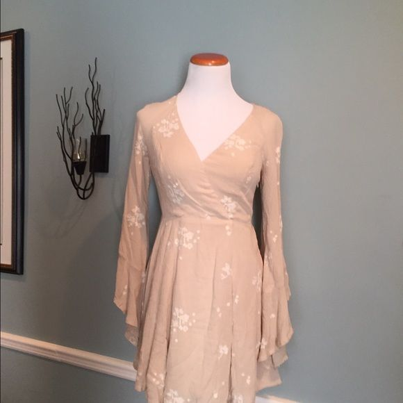 FREE PEOPLE DRESSmark down Beautiful Free People v-neck dress, NEW, tags on, pretty bell sleeves and slightly asymmetrical hem. Light tan with embroidered white flowers. Free People Dresses Mini