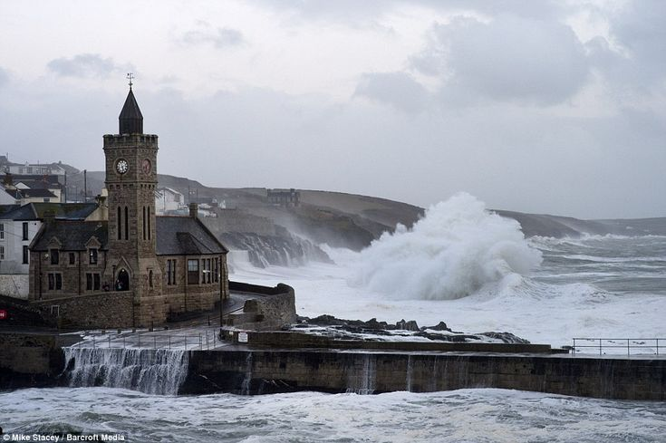 Incredibly high: Huge waves were seen drenching the coast of Porthleven in Cornwall today as waves are recorded at 63 feet at St Ives.