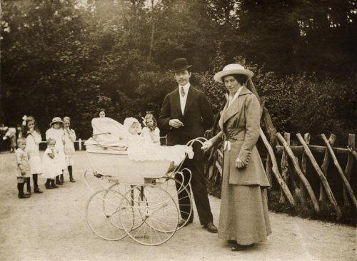 In een park staat een echtpaar bij een kinderwagen met hoge wielen, waar een kind inzit. De vrouw in een lang gewaad met hoed op staat samen met een man met een hoed en pak. Op de achtergrond staan kinderen toe te kijken. 1925. Plaats onbekend.