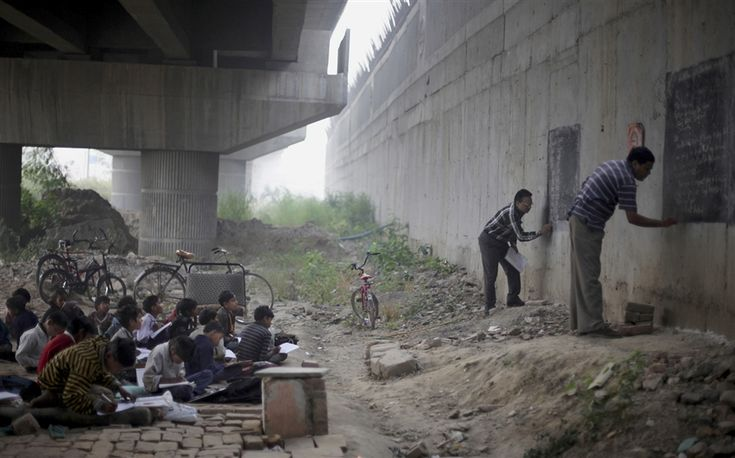 Founder of a free school for slum children Rajesh Kumar Sharma, second from right, and Laxmi Chandra, right, write on black boards, painted on a building wall, at a free school run under a metro bridge in New Delhi, India. At least 30 children living in the nearby slums have been receiving free education from this school for the last three years.
