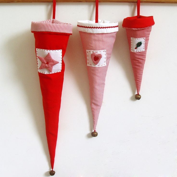 Fabric cones, decorated with handmade stitches and aheart, in red hues and a bell at the bottom.