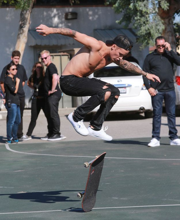9 Photos Of Justin Bieber Skateboarding Shirtless While Men Dressed In Black Stand Around Him, Watching