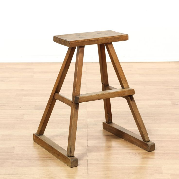 This Chinese style stool is featured in a solid wood with a distressed pine finish. This rustic stool has a slanted trestle base with stretchers and a simple seat with joinery accents. Perfect for a desk workstation! #asian #chairs #stool #sandiegovintage #vintagefurniture