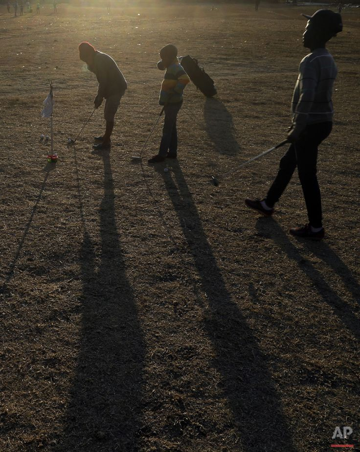 Children play a game of golf at a park in Katlehong township, east of Johannesburg, South Africa, Thursday, July 16, 2015. (AP Photo/Themba Hadebe)