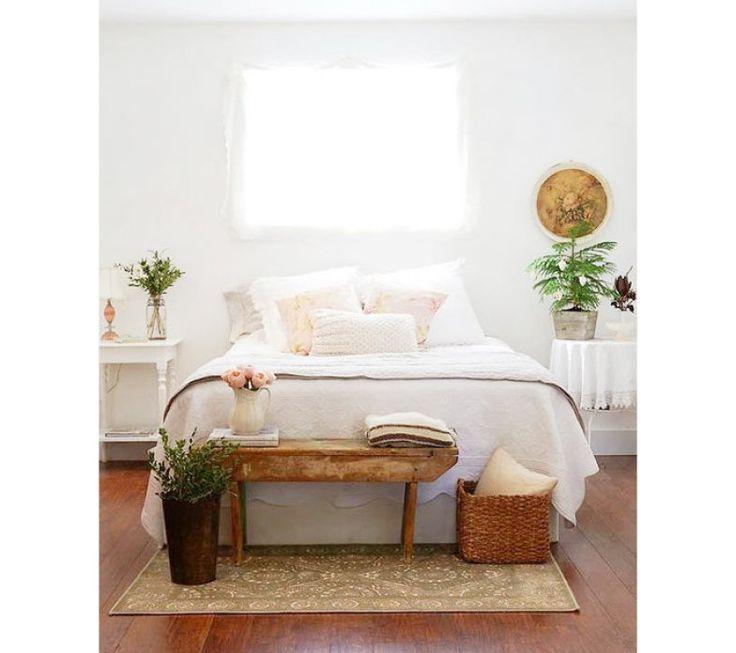 O banco escolhido era pequeno em relação à cama. A solução para garantir a proporção foi adotar um cesto de palha e um vaso de plantas, tudo sobre o tapete. Surgiu um ambiente pequeno e aconchegante, que quebra o branco predominante.