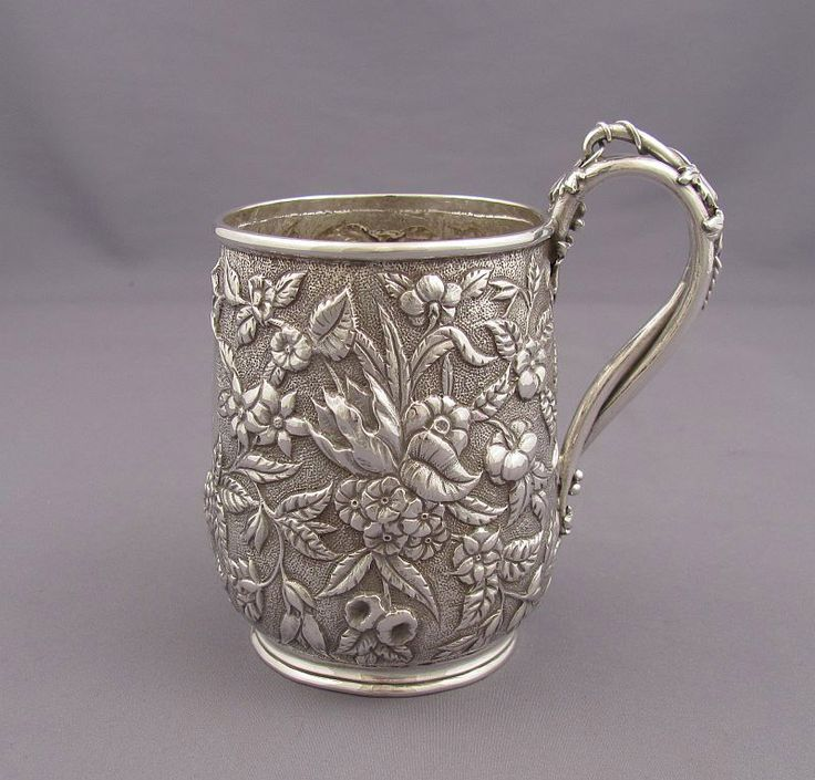 An antique youth-size silver mug by S.Kirk & Sons, Baltimore c. 1880-90.  Fine repoussé flowers and foliage on matte ground with...