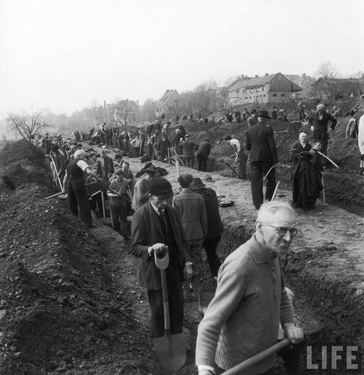 1945. Germany. German civilians being forced by the Canadian troops to give the victims of the concentration camp a proper burial.